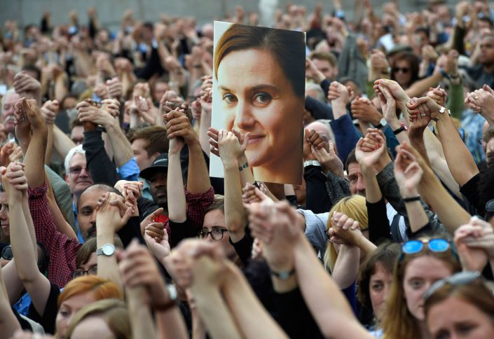 Hundreds of hands united and holding aloft the photo of Jo Cox